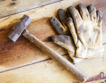 Photo of work gloves and a hammer on a wood surface