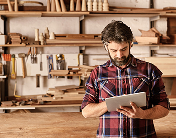 Photo of a man working on an iPad, with wood-working equipment in the background